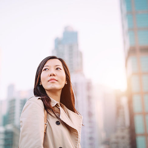Young Asian woman looking up with smile on a bright morning against city skyline